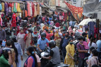 People wearing masks as a precaution against the coronavirus shop at a market upcoming Hindu festival Karwa Chauth in Jammu, India, Monday, Nov. 2, 2020. Married Hindu women eat this traditionally prepared food in the wee hours of the morning and fast till dusk during the festival, praying for health and long life of their husbands. (AP Photo/Channi Anand)