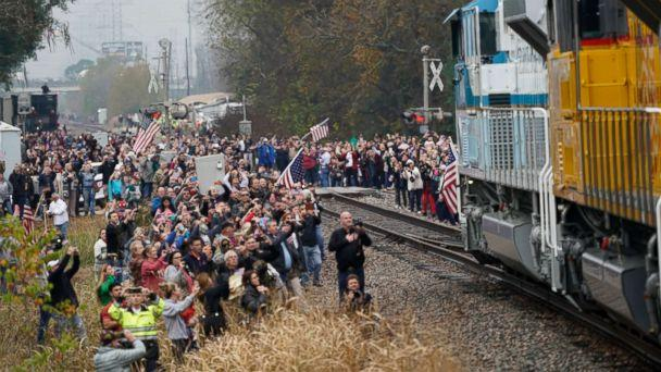 PHOTO: People pay their respects as the train carrying the casket of former President George H.W. Bush passes, Dec. 6, 2018, along the route from Spring to College Station, Texas. (David J. Phillip/Pool via AP)