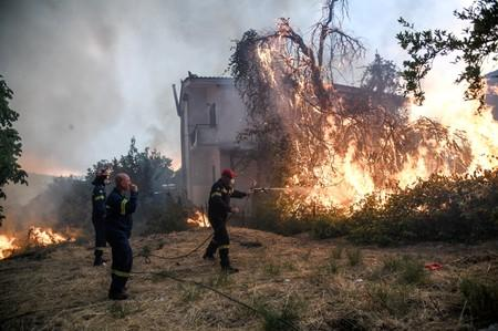 Firefighters try to extinguish a fire burning near a house as a wildfire burns at the village of Kontodespoti