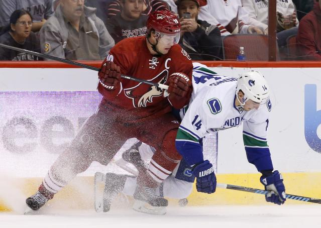 Vancouver Canucks' Alex Burrows (14) and Phoenix Coyotes' Shane Doan, left, collide as they go after the puck during the first period of an NHL hockey game on Tuesday, March 4, 2014, in Glendale, Ariz. (AP Photo/Ross D. Franklin)