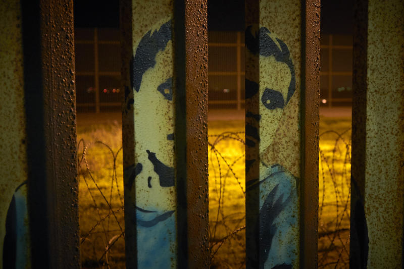 An image of a boy is painted on the bars of the border wall, in front of coils of razor wire Friday, Jan. 11, 2019, seen from Tijuana, Mexico. The partial government shutdown was on track Friday to become the longest closure in U.S. history as President Donald Trump and nervous Republicans looked for a way out of the mess. A solution couldn't come soon enough for federal workers who got pay statements Friday but no pay. (AP Photo/Gregory Bull)