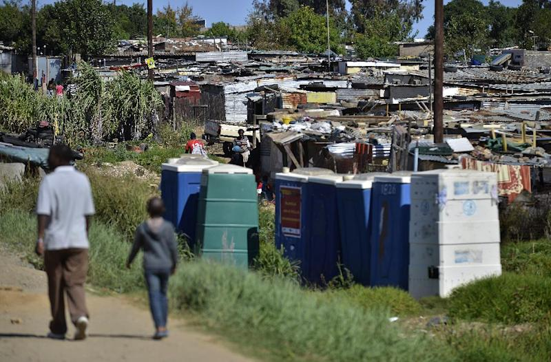 People walk by shacks in the impoverished township of Diepsloot on the outskirts of Centurion, South Africa, on April 24, 2014