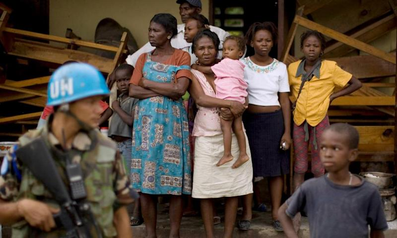 A UN peacekeeper stands guard while residents wait for food and medical treatment in a shelter in the Haitian town of Hinche