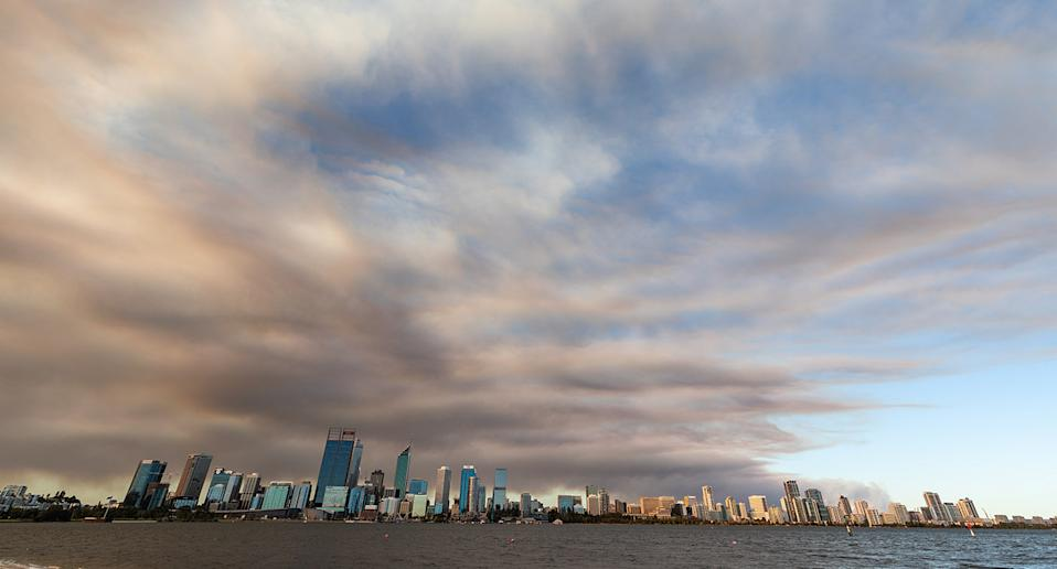 Smoke caused by a bushfire in the Perth hills suburb of Wooroloo rises behind the Perth city skyline on Monday, February 1, 2021. AAP Image/Richard Wainwright) NO ARCHIVING