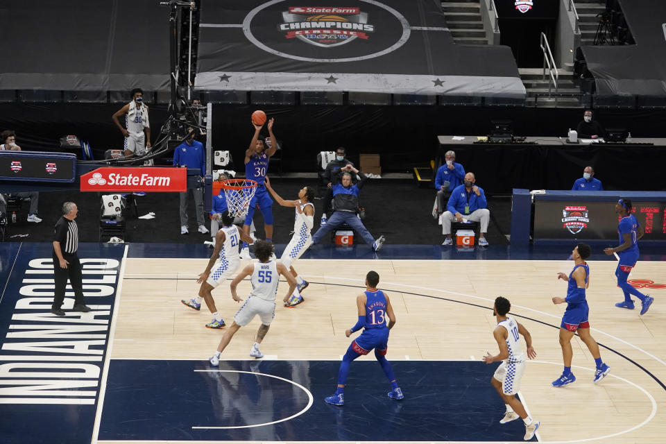 Kansas' Ochai Agbaji (30) puts up a shot against Kentucky's Cam'Ron Fletcher (21) during the first half of an NCAA college basketball game, Tuesday, Dec. 1, 2020, in Indianapolis. (AP Photo/Darron Cummings)