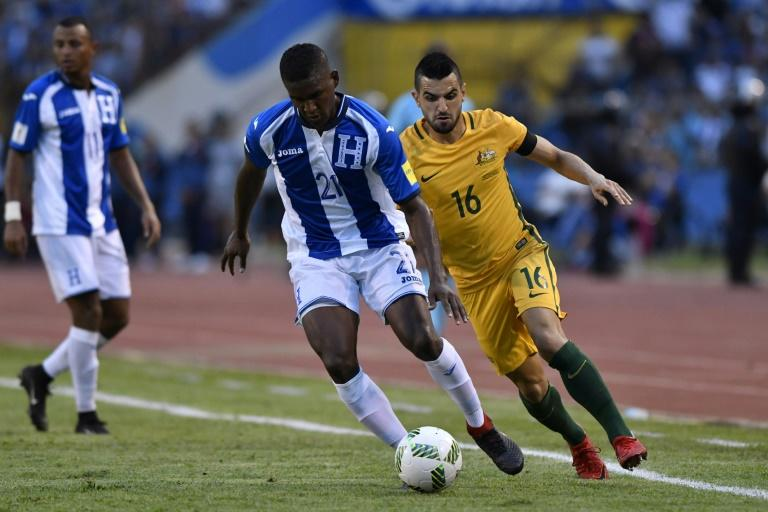 Honduras' Brayan Beckeles (C) drives the ball past Australia's Aziz Behich during their FIFA 2018 World Cup qualifying play-off first leg match, in San Pedro Sula, Honduras, on November 10, 2017