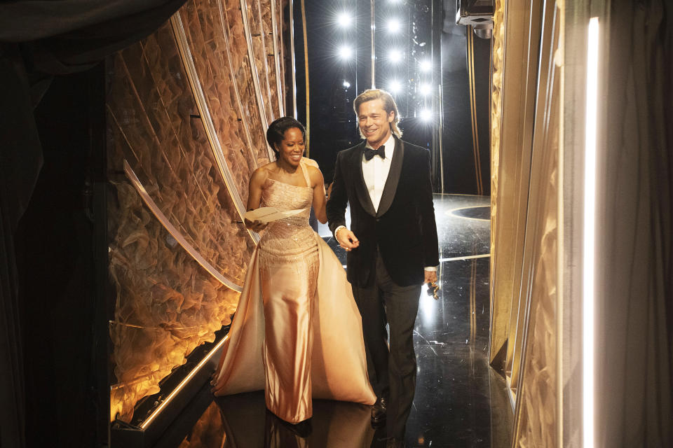 HOLLYWOOD, CALIFORNIA - FEBRUARY 09: In this handout photo provided by A.M.P.A.S. Regina King and Best Actor in a Supporting Role winner Brad Pitt walk backstage during the 92nd Annual Academy Awards at the Dolby Theatre on February 09, 2020 in Hollywood, California. (Photo by Richard Harbaugh - Handout/A.M.P.A.S. via Getty Images)