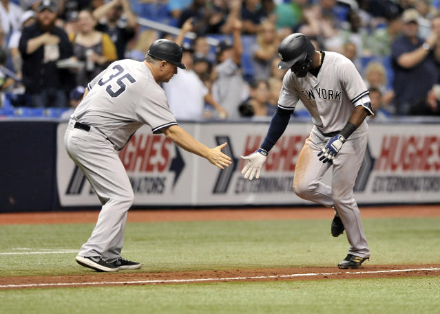 New York Yankees third base coach Phil Nevin (35) congratulates Adeiny Hechavarria after his solo home run off Tampa Bay Rays starter Jake Faria during the third inning of a baseball game Tuesday, Sept. 25, 2018, in St. Petersburg, Fla. (AP Photo/Steve Nesius)