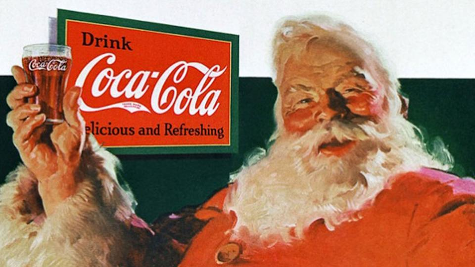 santa claus holding a glass of coca cola soda with a drink coca cola advertisement in the background