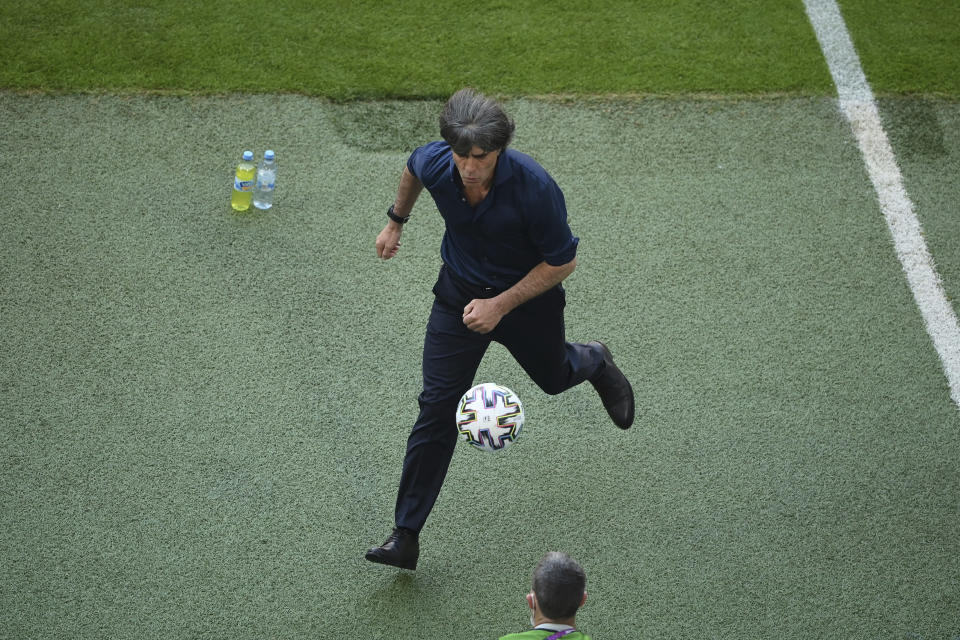 Germany's manager Joachim Loew collects the ball during the Euro 2020 soccer championship group F match between Portugal and Germany at the football arena stadium in Munich, Saturday, June 19, 2021. (Matthias Hangst/Pool Photo via AP)