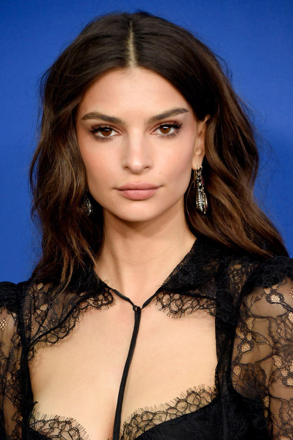 <p>For additional body around your roots when wearing curls, tip your hair upside down, apply voluminising spray and tuck the under layers of your hair behind your ears like Emily Ratajkowski. </p>