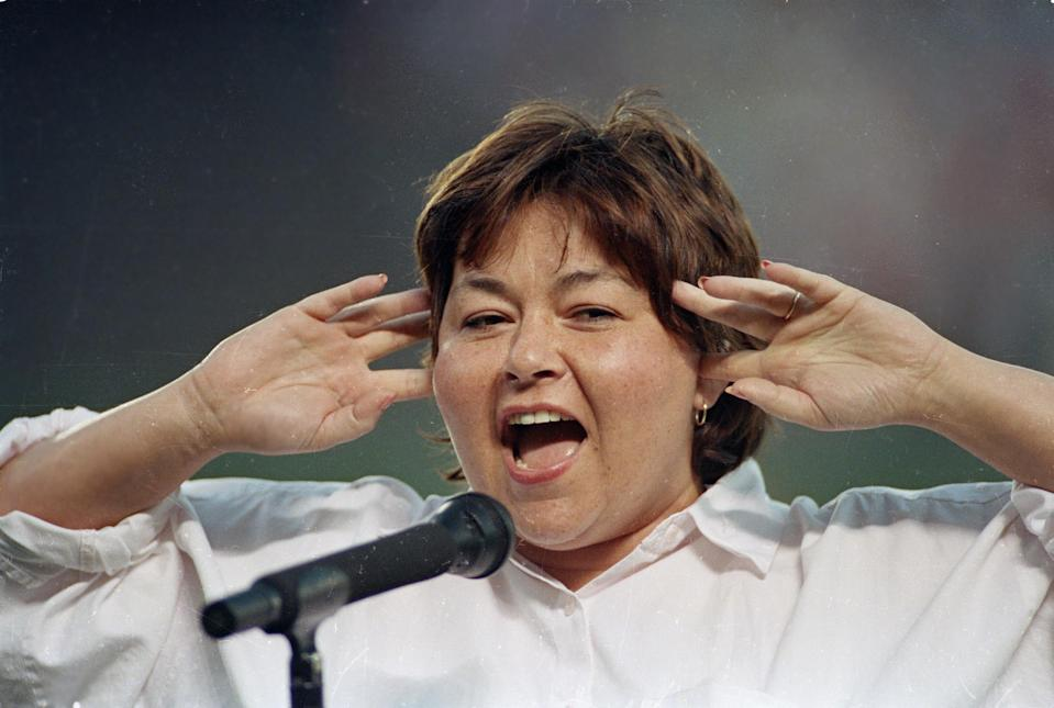 Roseanne Barr holds her fingers in her ears as she screams the national anthem between games of the San Diego Padres and the Cincinnati Reds doubleheader in 1990. She was booed loudly, and she made an obscene gesture and spat when she was finished. (Photo: AP Photo/Joan Fahrenthold)
