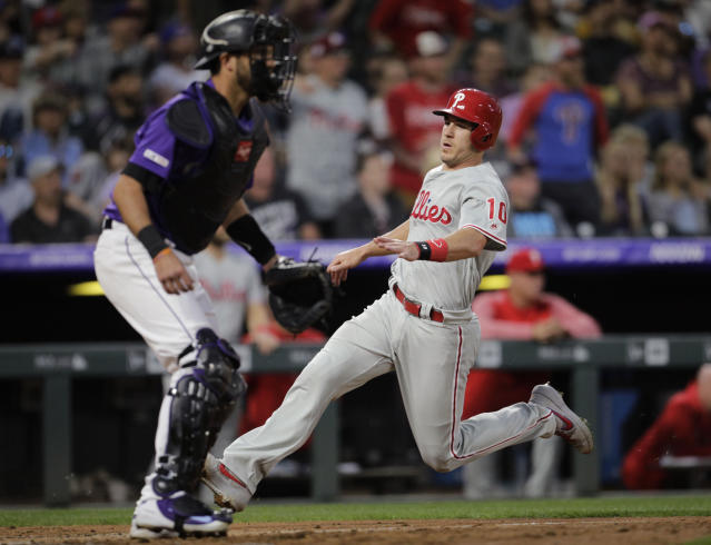 Philadelphia Phillies' J.T. Realmuto (10) scores against Colorado Rockies catcher Drew Butera (25) on a double by Phillies' Phil Gosselin in the fourth inning of a baseball game in Denver, Saturday, April 20, 2019. (AP Photo/Joe Mahoney)