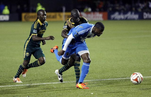 Philadelphia Union midfielder Maurice Edu, right, chases the ball towards the goal past Portland Timbers midfielder Diego Chara, left, and defender Pa Modou Kah during the first half of an MLS soccer game in Portland, Ore., Saturday, March 8, 2014. (AP Photo/Don Ryan)