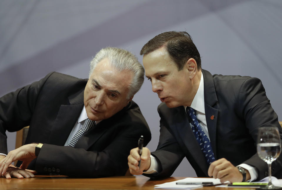 Brazil's President Michel Temer, left, leans over to listen to Sao Paulo Mayor Joao Doria, during a ceremony to announce the creation of a new park and museum at the City Hall, in Sao Paulo, Brazil, Monday, Aug. 7, 2017. (AP Photo/Andre Penner)