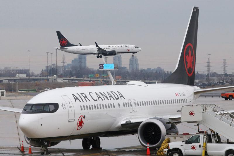 An Air Canada Boeing 737 MAX 8 from San Francisco approaches for landing at Toronto Pearson International Airport over a parked Air Canada Boeing 737 MAX 8 aircraft in Toronto