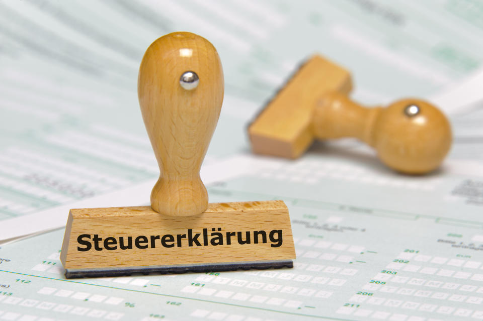 rubber stamp marked with tax declaration in german language - Steuererklärung - over documents and tax forms