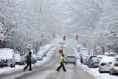 A snow shoveler crosses a street during a winter snowstorm in Cambridge, Massachusetts January 24, 2015. REUTERS/Brian Snyder