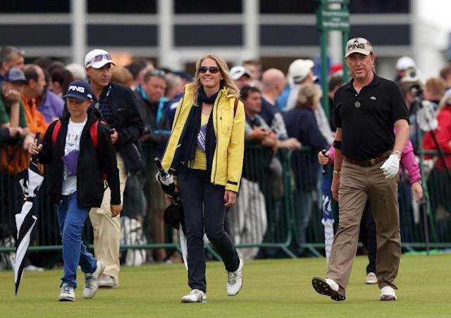 Miguel Angel Jimenez of Spain walks down the 3rd fairway with his wife and son during a practice round ahead of the British Open Golf championship at the Royal Liverpool golf club, Hoylake, England, Wednesday July 16, 2014. The British Open Golf championship starts Thursday July 17. (AP Photo/Jon Super)