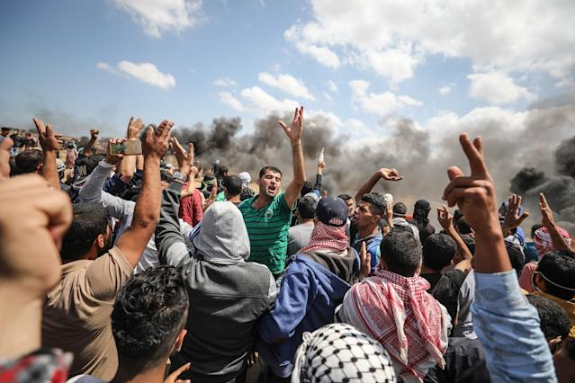<p>Palestinians carry an injured protester after Israel's intervention during a protest to mark the 70th anniversary of Nakba, also known as Day of the Catastrophe in 1948, and against the relocation of the U.S. Embassy from Tel Aviv to Jerusalem, near Gaza-Israel border in Khan Younis on May 14, 2018. (Photo: Mustafa Hassona/Anadolu Agency/Getty Images) </p>
