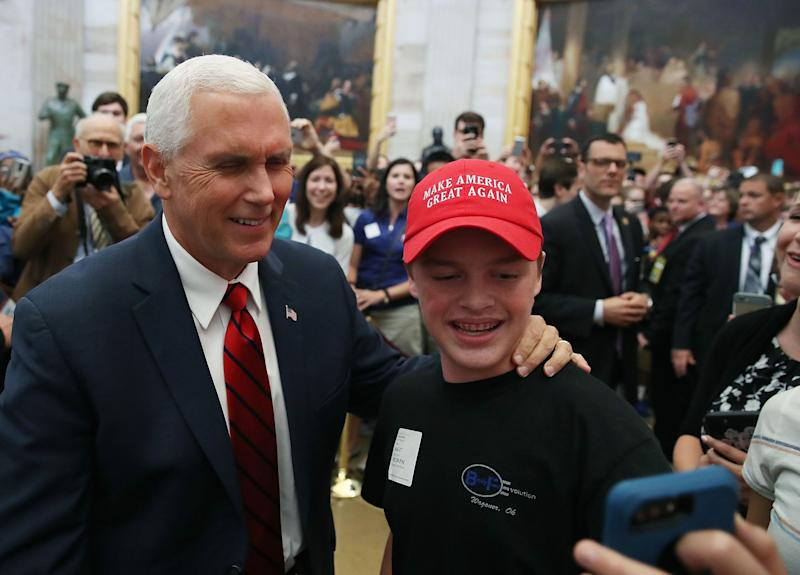 "Vice President Mike Pence takes a selfie with a tourist wearing a ""Make America Great Again"" hat inside the U.S. Capitol rotunda on June 6, 2017. The vice president walked through the rotunda after attending the Senate Republican policy luncheon."