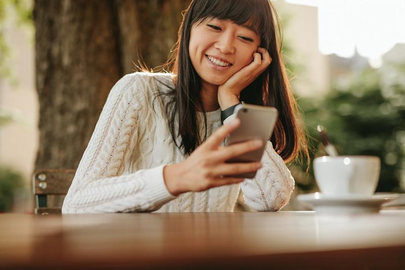 Asian woman smiling while holding smartphone.
