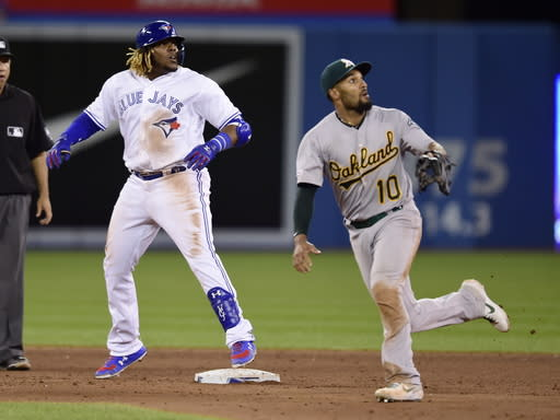Toronto Blue Jays' Vladimir Guerrero Jr., front left, is safe at second on a double as Oakland Athletics shortstop Marcus Semien (10) looks on during ninth-inning baseball game action in Toronto, Friday, April 26, 2019. (Frank Gunn/The Canadian Press via AP)
