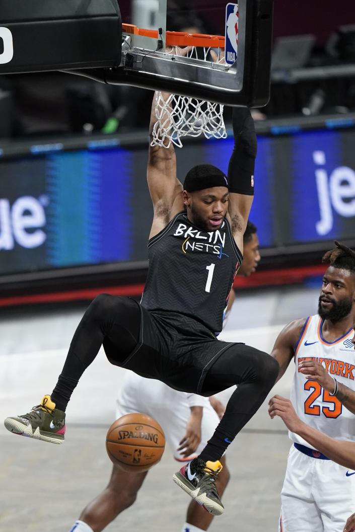Brooklyn Nets' Bruce Brown (1) dunks the ball in front of New York Knicks' Reggie Bullock (25) during the first half of an NBA basketball game Monday, April 5, 2021, in New York. (AP Photo/Frank Franklin II)
