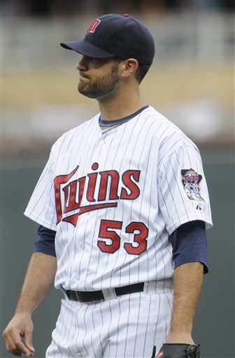 Minnesota Twins pitcher Nick Blackburn reacts as he watches the solo home run off Tampa Bay Rays' Matt Joyce in the first inning of a baseball game Saturday, Aug. 11, 2012 in Minneapolis. Moments before, he gave up a two-run home run to B.J. Upton. (AP Photo/Jim Mone)