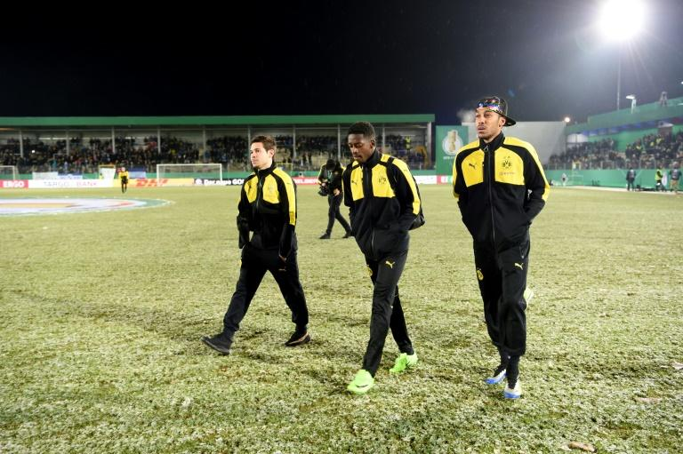 Dortmund's (from L) Raphael Guerreiro, Ousmane Dembele and Pierre-Emerick Aubameyang walk accross the pitch after their cancelled German Cup match against Sportfreunde Lotte due to heavy snowfall, in Lotte, on February 28, 2017