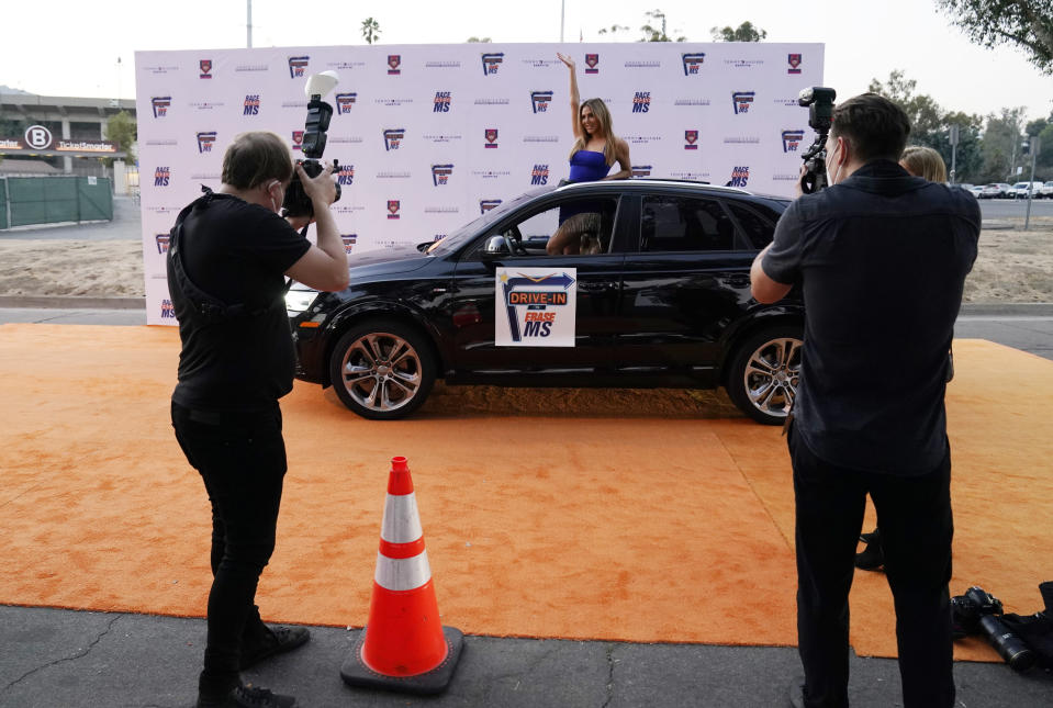 Photographers maintain social distance as they shoot guests arriving in a car on the orange carpet at the Drive-In to Erase MS gala, Friday, Sept. 4, 2020, in Pasadena, Calif. (AP Photo/Chris Pizzello)