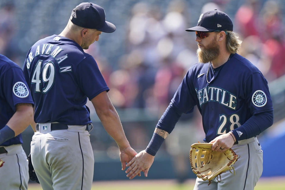 Seattle Mariners' Jake Fraley (28) and Kendall Graveman (49) celebrate after they defeated the Cleveland Indians in a baseball game, Sunday, June 13, 2021, in Cleveland. (AP Photo/Tony Dejak)