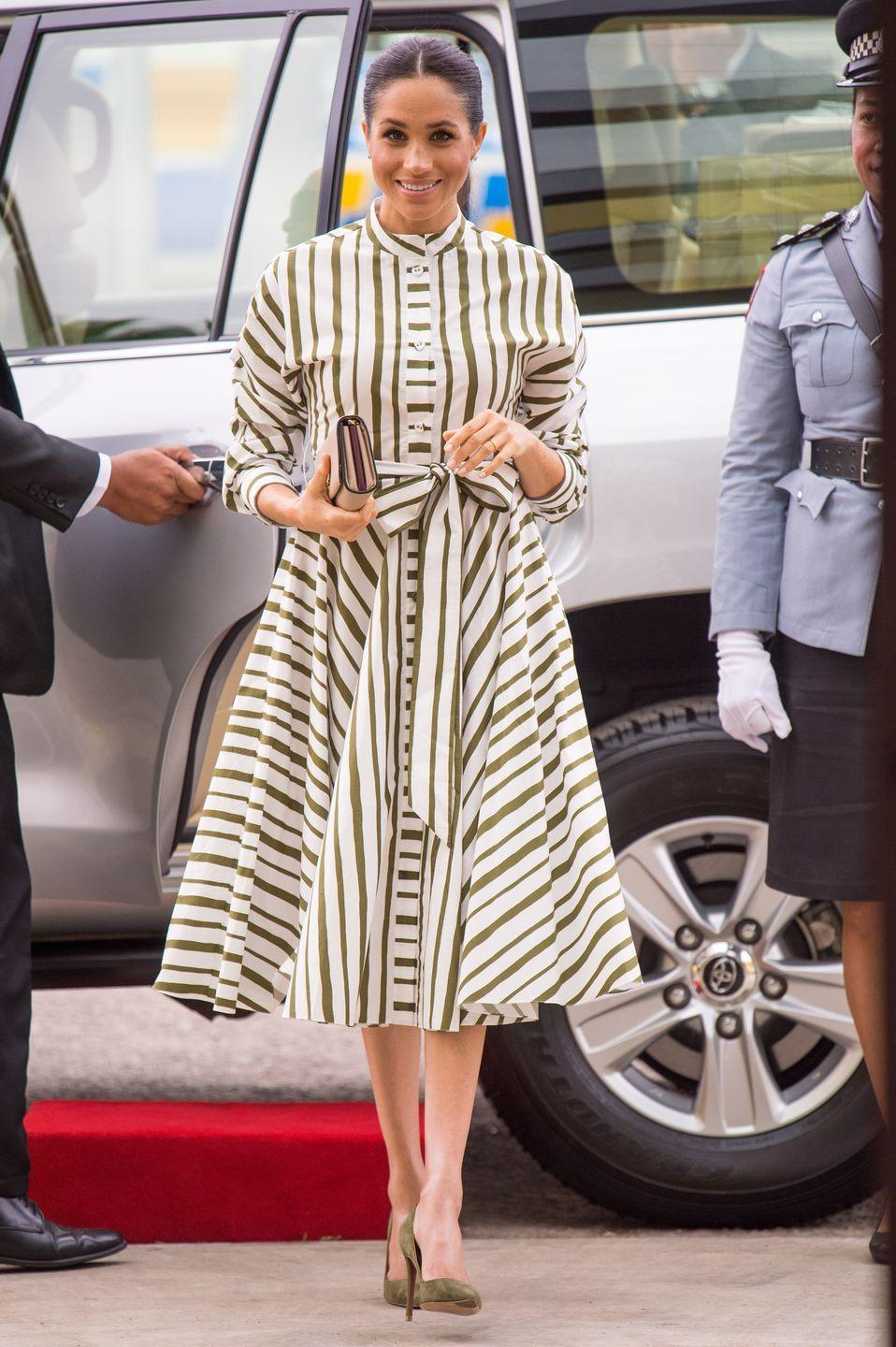 <p>Meghan kicked off her second day in Tonga wearing a striped dress by Martin Grant. She finished her outfit off with a clutch by Prada and green heels. </p>