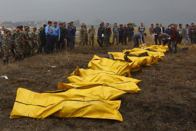 <p>Nepalese rescuers attend to bodies of victims after a passenger plane from Bangladesh crashed at the airport in Kathmandu, Nepal, March 12, 2018. (Photo: Niranjan Shreshta/AP) </p>