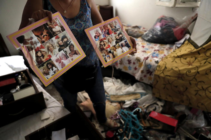 Image: A woman shows pictures of her family in her damaged home (Hussein Malla / AP)
