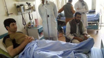 In this undated photo provided by Ryan Brummond, Mohammad Khalid Wardak, left, receives medical attention at a hospital in Afghanistan. Khalid, as he's called by his friends, had no intention of leaving Afghanistan, where he was a high-profile national police officer who'd worked alongside American special forces to defeat the Taliban. Then with stunning speed, his government collapsed. Now he is in hiding with his wife and four children, wounded and hunted by the Taliban, desperately hoping that American officials will repay his loyalty by helping his family escape almost certain death. (Ryan Brummond via AP)