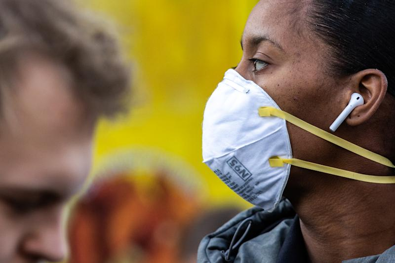 A new report from the CDC suggests the coronavirus may be spread before the onset of symptoms. Here a woman wearing a protective mask is seen in New York. (Photo by Jeenah Moon/Getty Images)