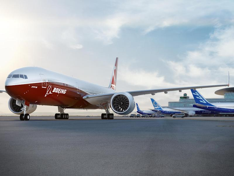 One red Boeing aircraft on an airport ramp with three others in the background.