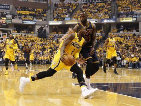 Apr 20, 2017; Indianapolis, IN, USA; Indiana Pacers guard C.J. Miles (0) drives to the basket against Cleveland Cavaliers forward LeBron James (23) in game three of the first round of the 2017 NBA Playoffs at Bankers Life Fieldhouse. Mandatory Credit: Brian Spurlock-USA TODAY Sports