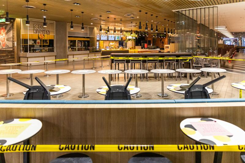 An empty foodcourt with chairs stack on tables and caution taped around a Melbourne dining hall.