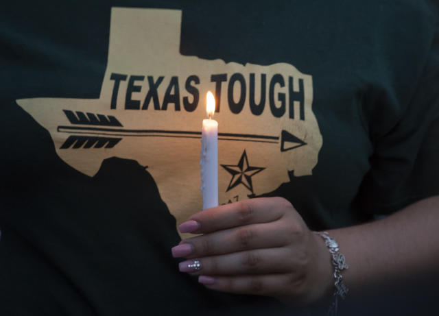 <p>A woman wearing a Texas t-shirt holds a lighted candle during a vigil held in the wake of a deadly school shooting at Santa Fe High School on Friday, May 18, 2018, in Galveston, Texas. (Photo: Stuart Villanueva/The Galveston County Daily News via AP) </p>