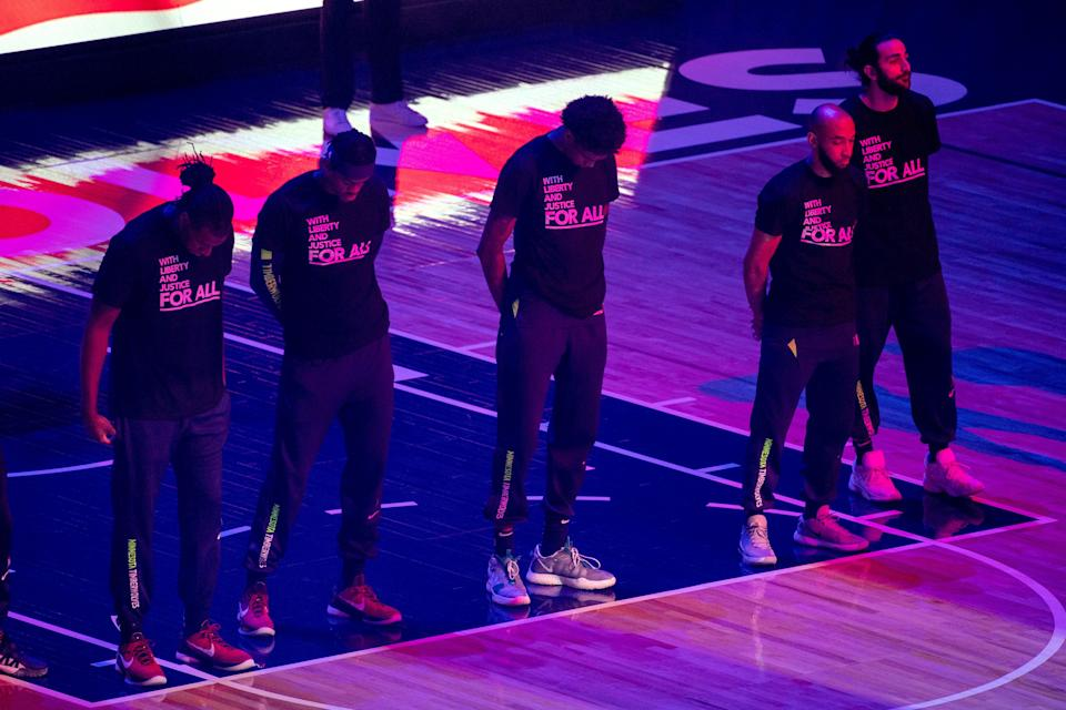 """Members of the Minnesota Timberwolves wear T-shirts that read """"With liberty and justice FOR ALL"""" as a tribute to Daunte Wright before their game against the Brooklyn Nets."""