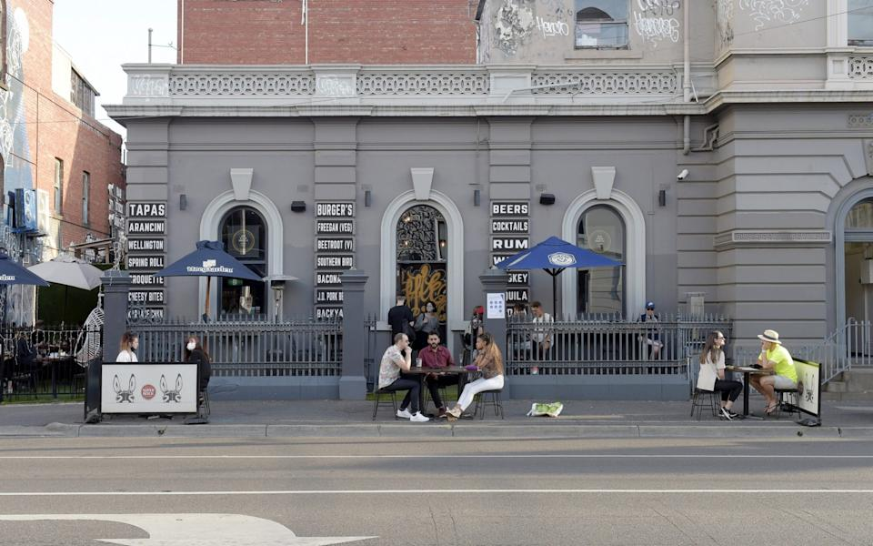 Customers sit at socially distanced tables outside a restaurant in the Fitzroy suburb of Melbourne - Bloomberg