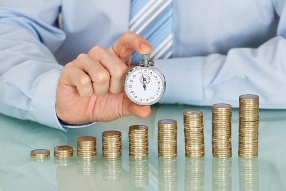 A man with a stopwatch held in front of a growing stack of coins.