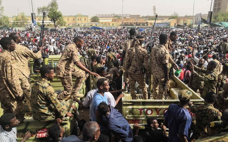 Sudanese soldeirs stand guard on armoured military vehicles as demonstrators continue their protest - AFP