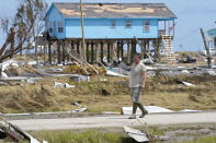 Jim Venissat, who's camp was destroyed by Hurricane Laura, walks amid the devastation in Holly Beach, La., Saturday, Aug. 29, 2020. (AP Photo/Gerald Herbert)