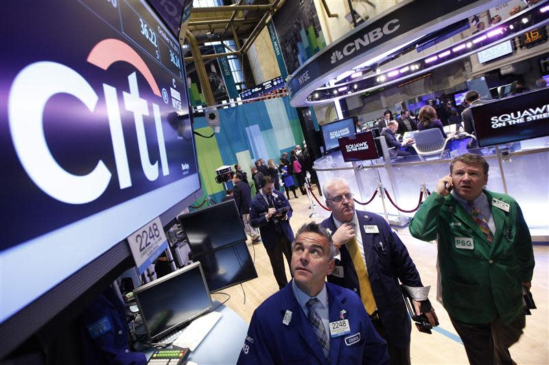 Traders work at the trading post that trades Citigroup stock on the floor of the New York Stock Exchange in this file photo