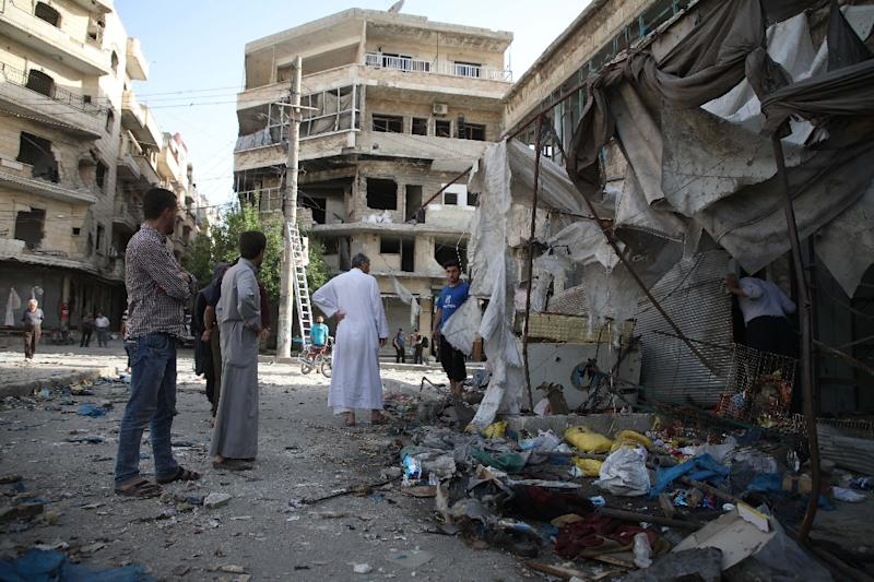 Maarat al-Numan residents survey the remains of stalls in the town's market after it was hit by suspected Syrian government air strikes that killed 12 civilians the previous evening (AFP Photo/Aaref WATAD)
