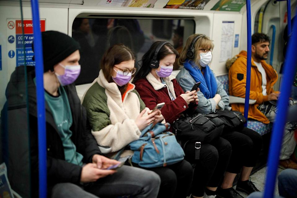 Commuters wear masks as a precaution whilst travelling on a London Underground Tube train on Wednesday (AFP via Getty Images)