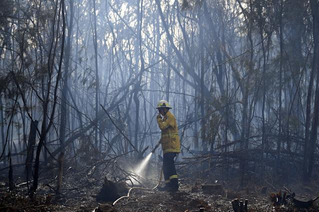 A firefighter doses a bushfire in the residential area of Sydney on November 12, 2019. - Bushfires raging across eastern Australia on November 12 singed the Sydney suburbs, where firefighters were forced to scramble planes and helicopters to splatter a built-up neighbourhood with water and red retardant. (Photo by Saeed KHAN / AFP) (Photo by SAEED KHAN/AFP via Getty Images)